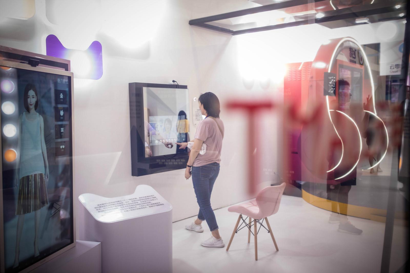 图为:消费者正在体验天猫推出虚拟试衣等新零售创新购物服务。_meitu_2