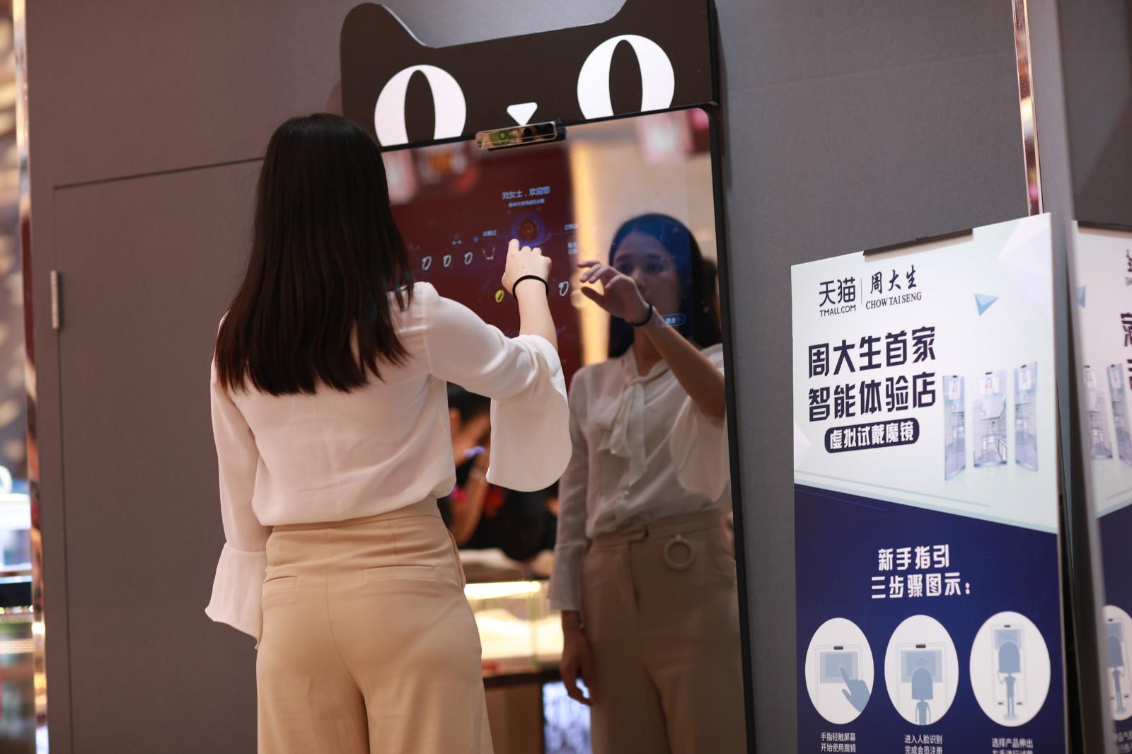 """在深圳周大生智能体验店内,一位导购员正在""""智能魔镜""""前操作如何进行饰品的""""虚拟试戴""""体验。_meitu_2"""