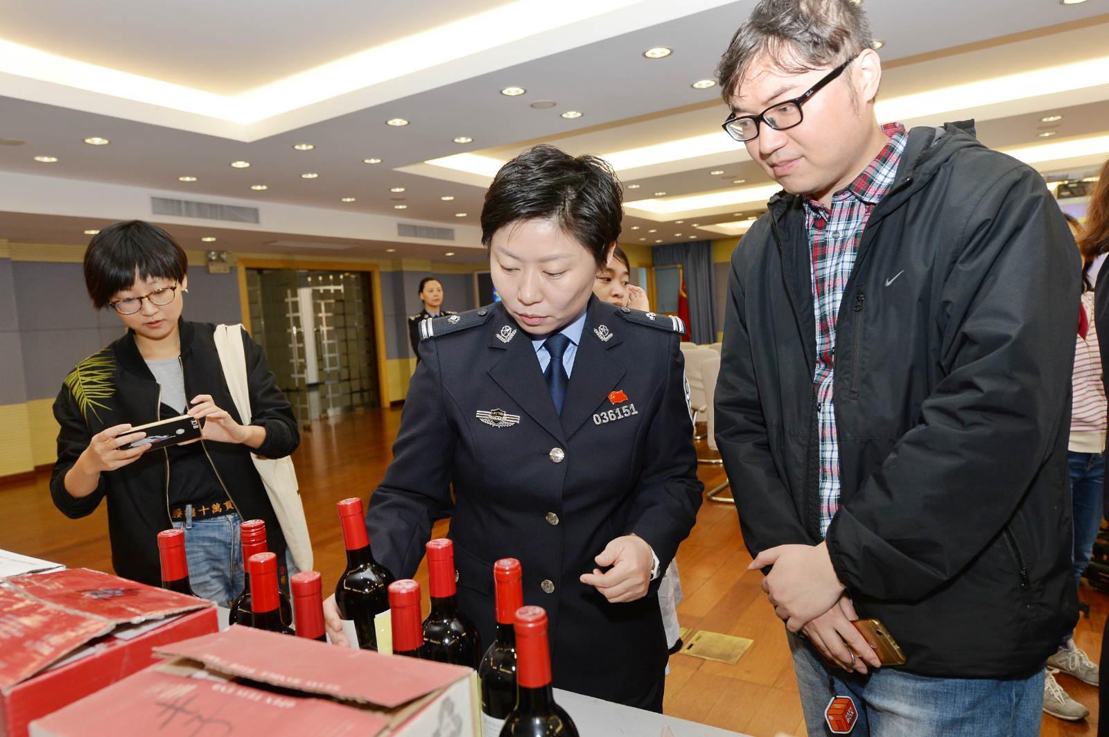 图说:警方向记者介绍,假酒在外包装上就很容易辨别真伪。_meitu_4