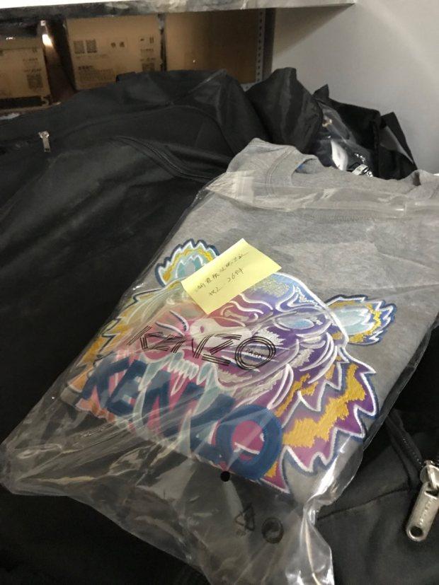 图说:警方从刘某的线下售假窝点查获的假冒KENZO品牌卫衣。