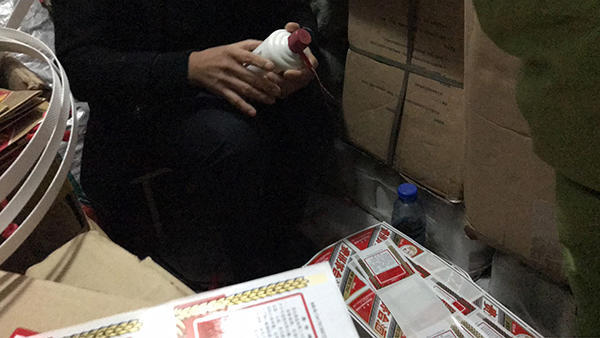媒体暗访曝光假茅台灌装制作过程,图为制假者在地下室包装假茅台酒。