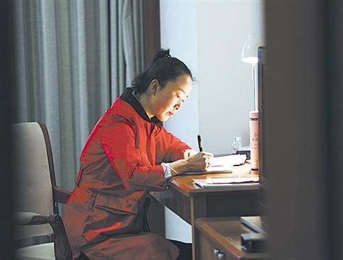 3月3日,全国人大代表、农村电商创业者梁倩娟在驻地准备发言稿。