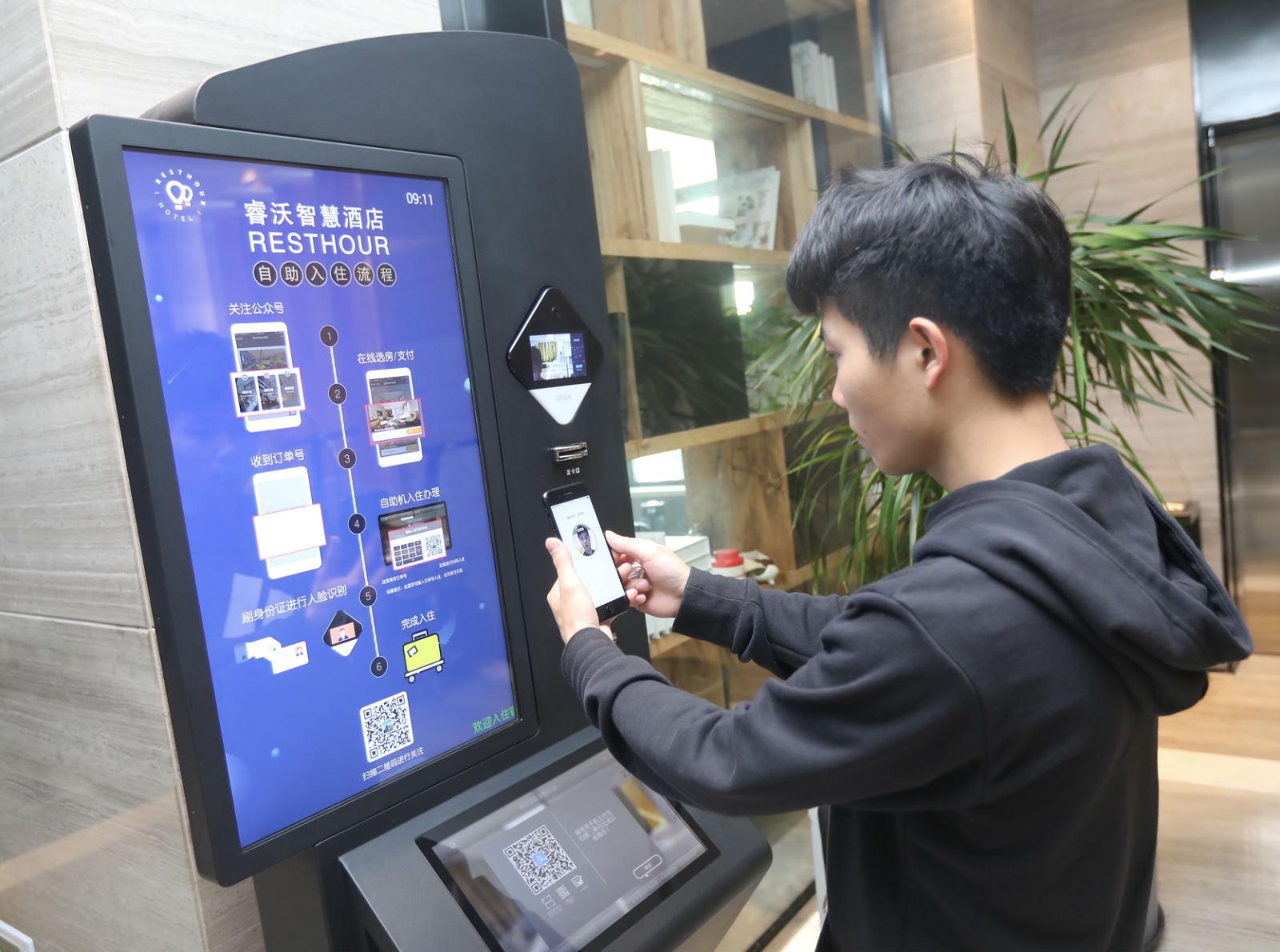 """4月17日,杭州睿沃智慧酒店,一名旅客体验使用支付宝内的""""网证""""办理酒店入住登记。_meitu_3"""