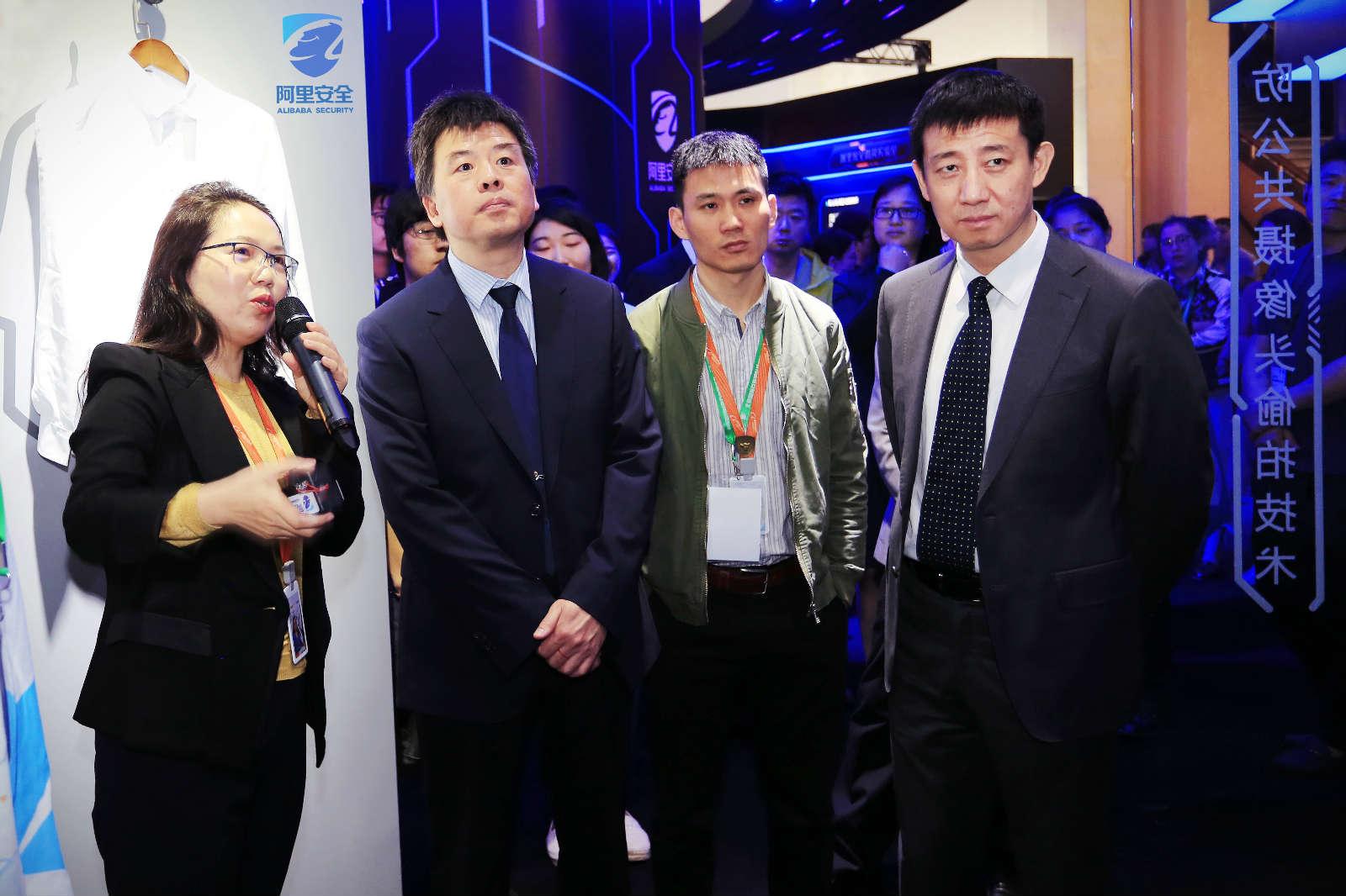 4月27日,阿里巴巴集团首席风险官郑俊芳(左一)在阿里展区向公安部网络安全保卫局副局长钟忠(左二)、北京市公安局副局长张健(右一)介绍阿里安全八大实验室的核心技术能力_meitu_6