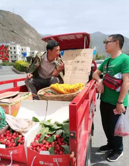 一位路人象征性地装了一把樱桃,认真听着陈光书讲述地震后的生活变化。
