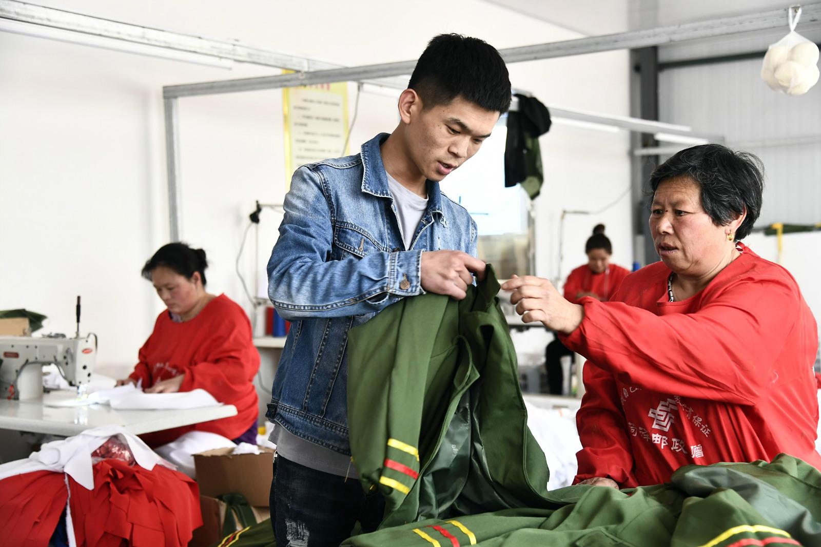 图4 山东大学毕业的姜彪回到大集镇开起了演出服淘宝店,正在和工人沟通_meitu_10