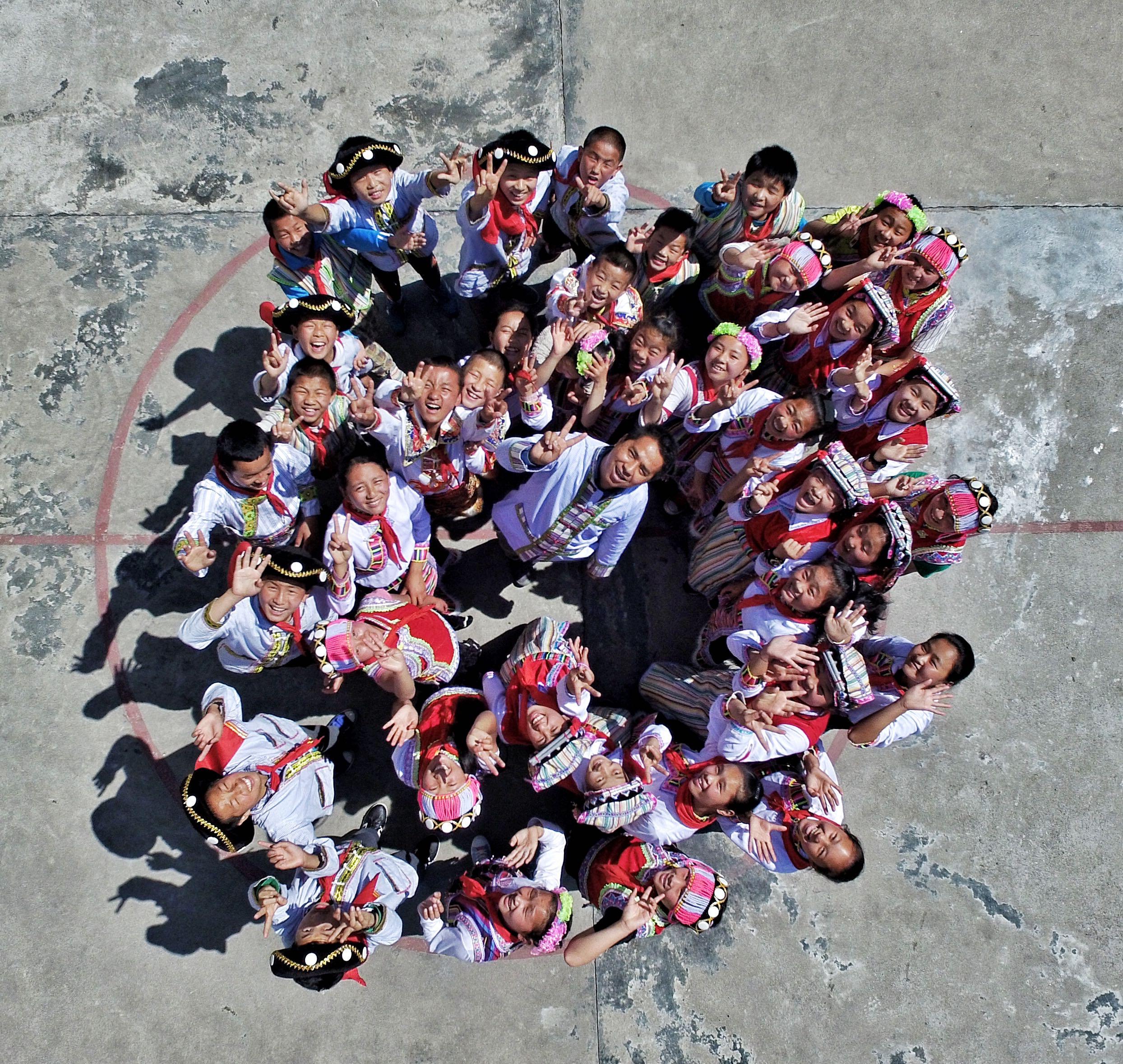 云南怒江。贡山县捧当乡,桑磊和孩子们在一起。(王警 摄)1