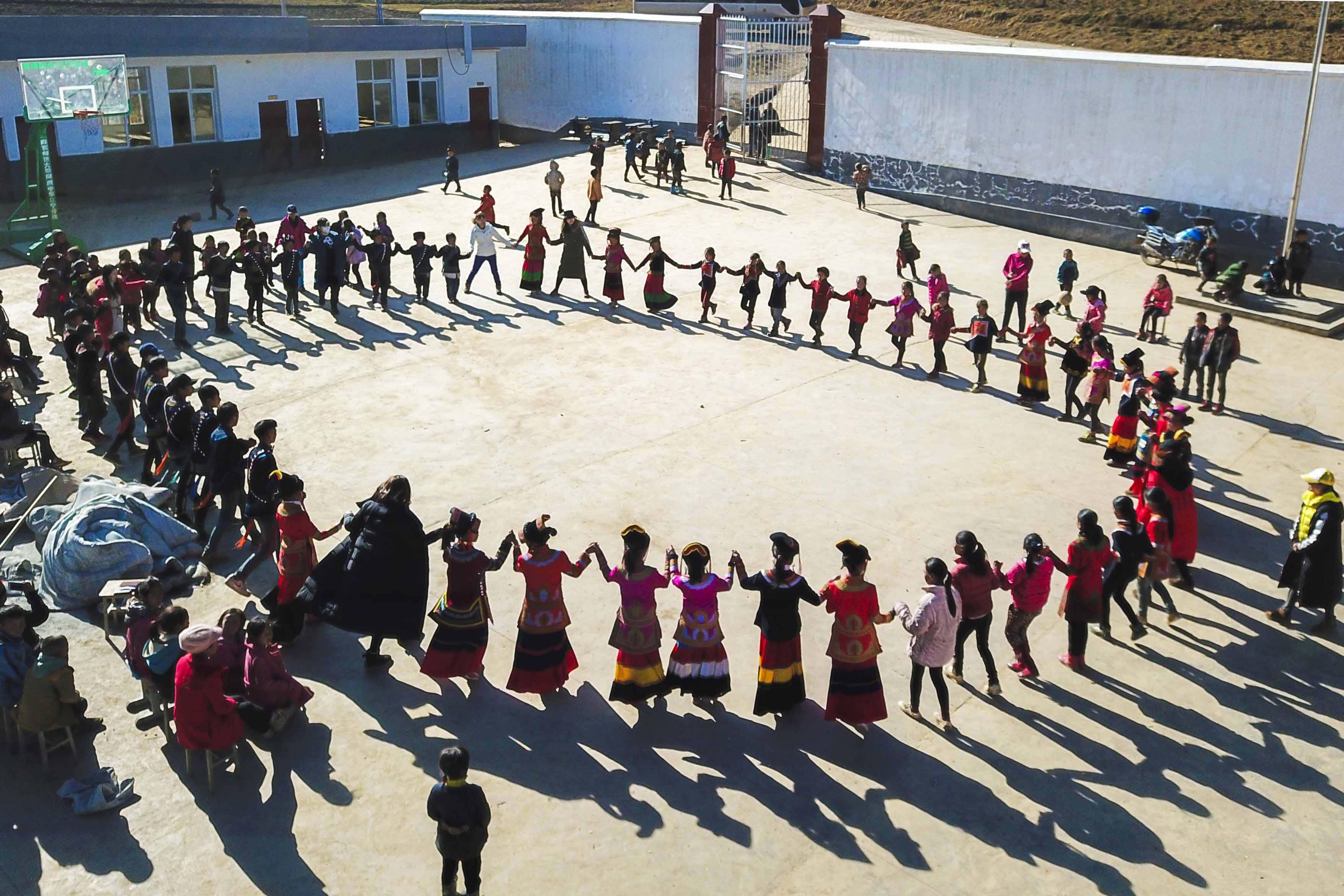 2017年12月31日,四川昭觉,瓦吾教学点的孩子们与前来支教的志愿者们跳舞互动。