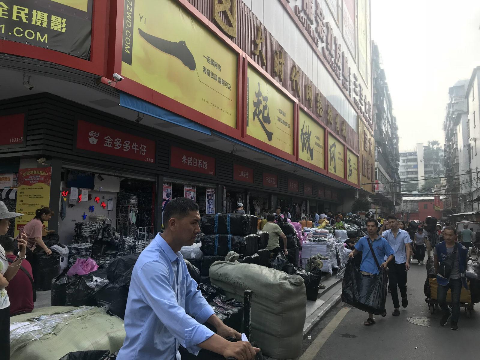 图说:大时代网络批发城一楼的档口外,摆满了准备运到淘宝店主仓库的衣服_meitu_4