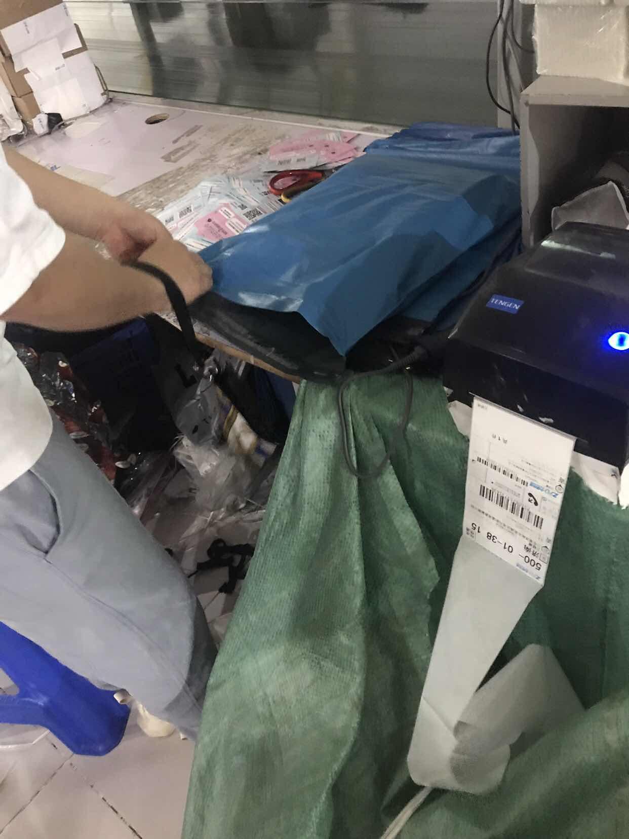 图说:王明给即将寄出的服装打包。