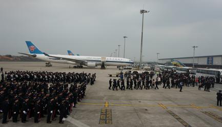 图说:233名犯罪嫌疑人从3辆民航包机上下来后,再通过大巴押解至深圳、珠海等地。